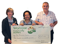 Three people holding a very large cheque