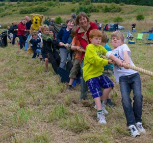 A group of around 15 children and adults pulling hard on a tug of war rope in a grassy field.