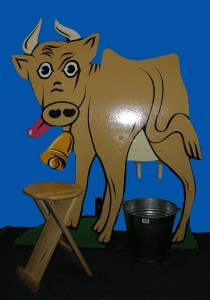 a wooden cow-shaped board with 'udders', shown with a wooden stool and metal bucket