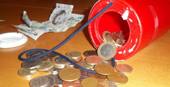 Collection tin with coins spilling out of it and notes in the background.