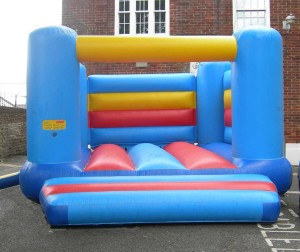 Bouncy castle with two sides and a back, and an inflatable 'step' at the entrance. A label on the bouncy castle reads Users: maximum height 1.5m, maximum number 8.