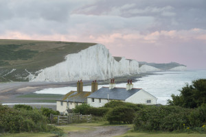 Stormy skies over the coastgard cottages at Cuckmere Valley, East Sussex, with the Seven Sisters seen beyond.