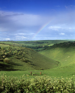 A long, curved valley between two hills, with a rainbow faintly appearing in background.