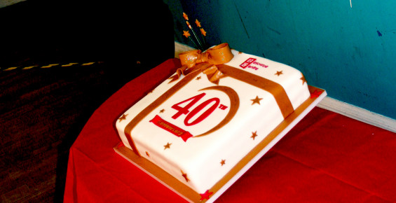 Square white cake with 40 in large red lettering and a gold bow